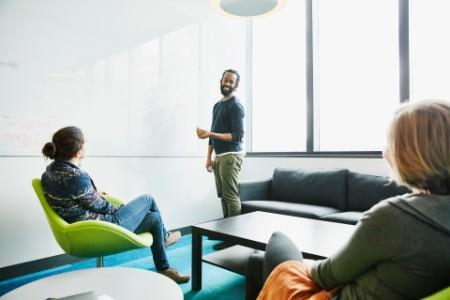 Un científico sonriente discutiendo datos con sus colegas en la sala de conferencias del laboratorio de investigación