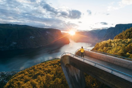 Tourist admiring the sunset over norwegian fjord, Norway