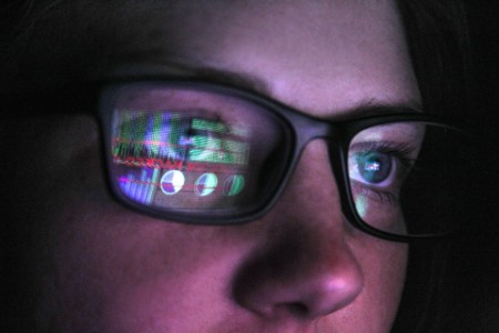 Woman looking at computer screen in darkness