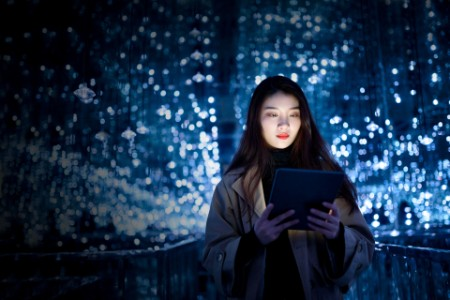woman using digital tablet against illuminated background