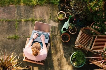 Mulher trabalhando no laptop no jardim