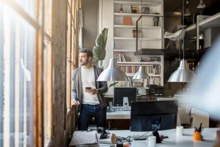 joven empresario mirando a través de la ventana de la oficina