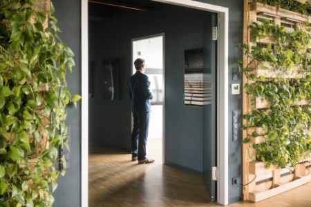 A businessman standing at the door in a green office