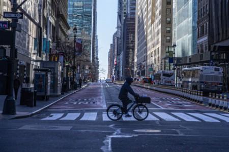 A person rides his bike through the near empty streets near grand central