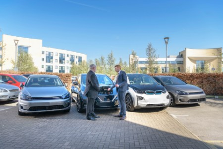 Businessmen looking at range of electric cars