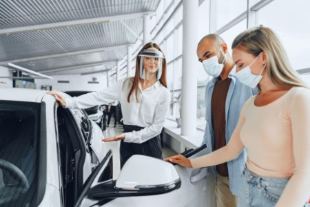 Car dealer consulting buyers wearing medical face shield