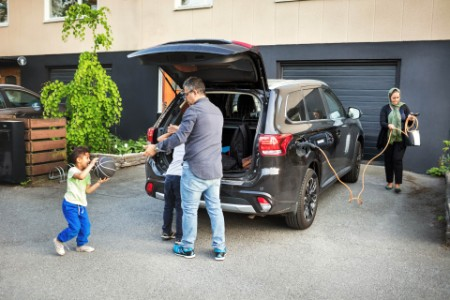 Father playing with children by electric car at home
