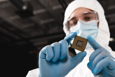 Microchip in hands of scientist wearing latex gloves