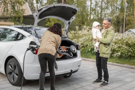 Parents loading pram into car boot