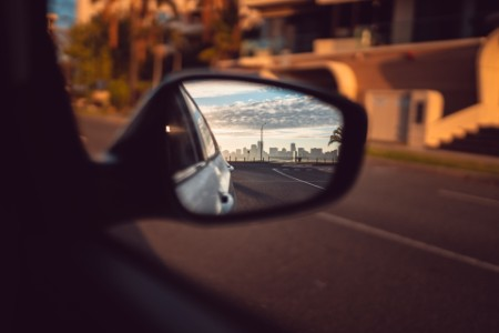 Perth city skyline in the sideview mirror of a car