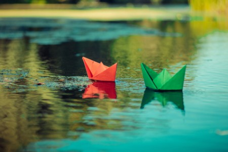 Red and green paper boats on a river
