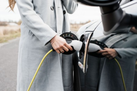 Woman hand plugging in charging lead to her electric car