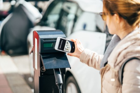Woman paying contactless for charging an electric car