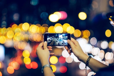 Woman photographing night scene smartphone