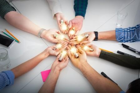 Team holding light bulbs