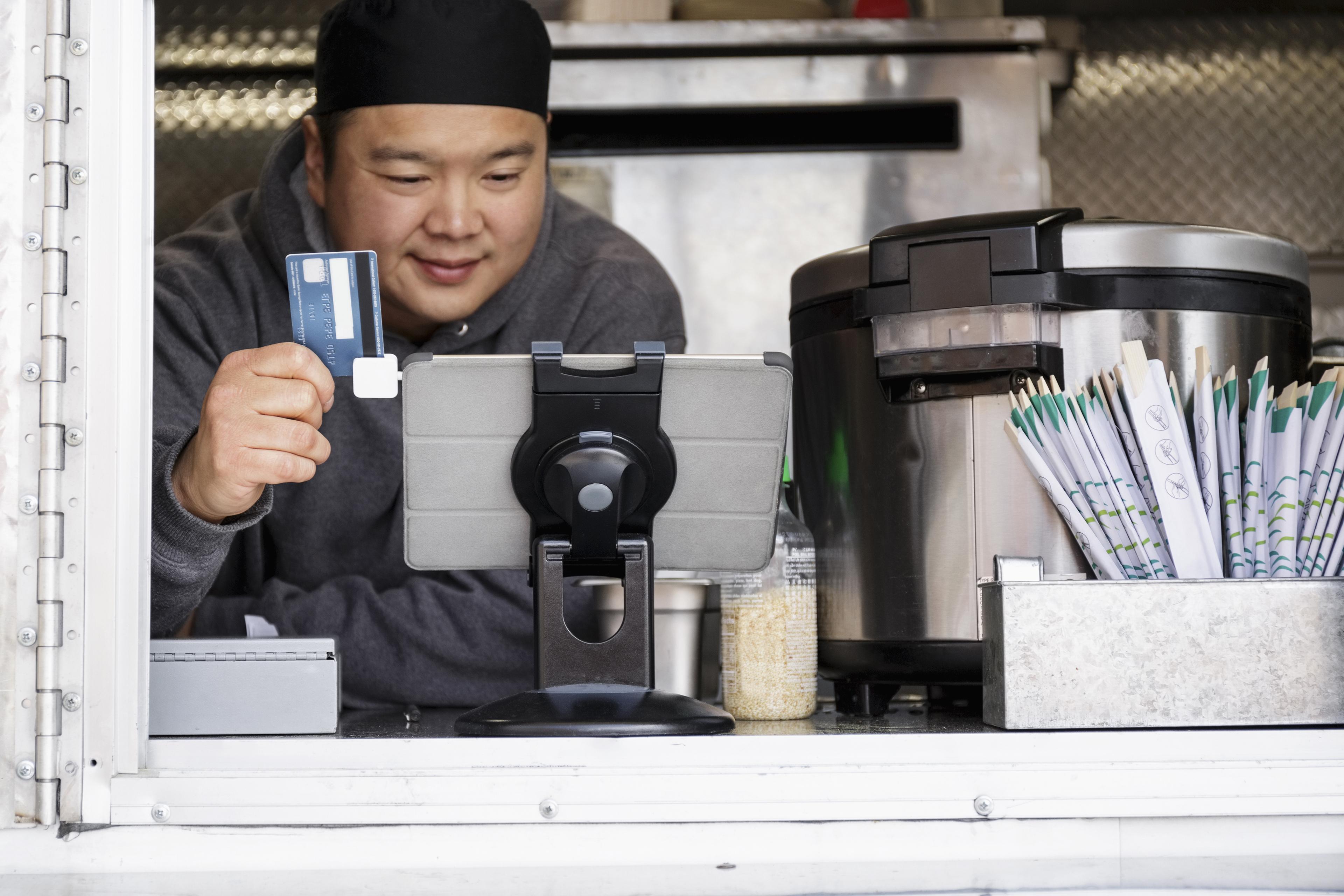 asian man processing credit card digital tablet food cart