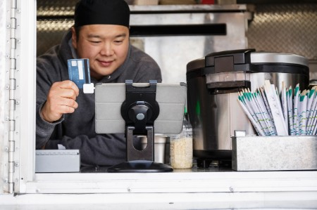Asian man processing credit card digital tablet food cart