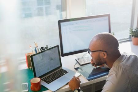 Designer working at laptop office desk