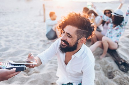 Smiling man paying with smartphone on beach