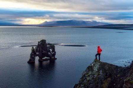 A man standing below dinosaur rock hvitserkur iceland