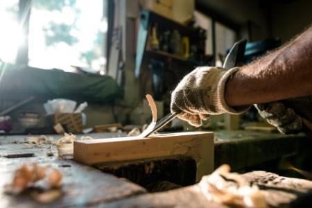 An experienced carpenter shapes wood with a chisel