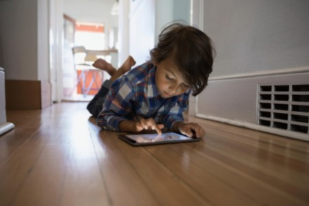 Boy using digital tablet hallway floor