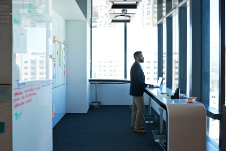 businessman looking out of window in open office