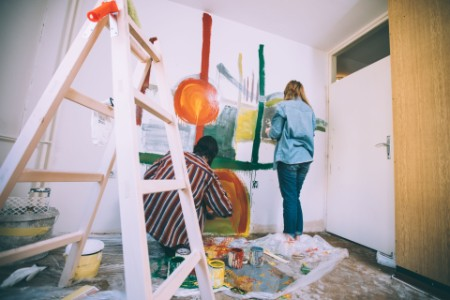 Couple painting an abstract painting on wall together