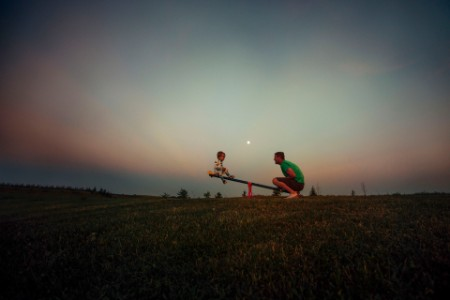 father and son playing on seesaw against sky at dusk