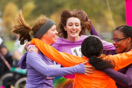 Female runners finishing charity run celebrating