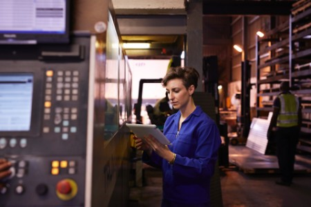 Female steel worker holding tablet inside factory