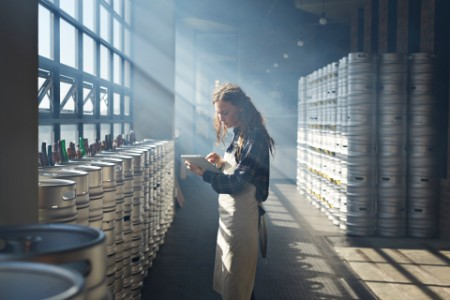 Female waiter counting kegs using tablets