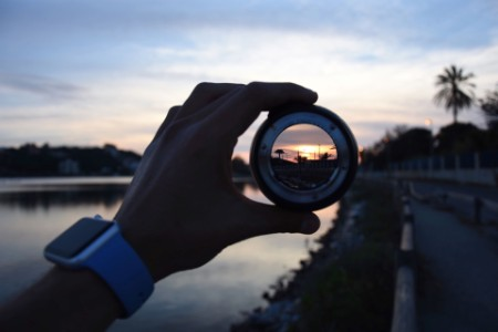 Hand holding camera lens looking at sunset