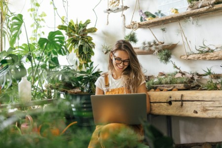 Happy young woman using laptop in a gardening shop