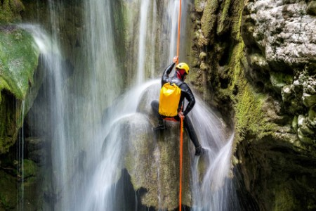 Man canyoneering backpack rappeling down waterfall in canyon