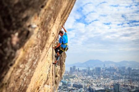 Hombre escalando el cielo azul de Hong Kong