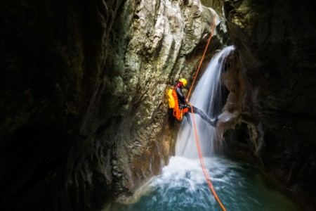 Man on canyoning adventure on waterfall