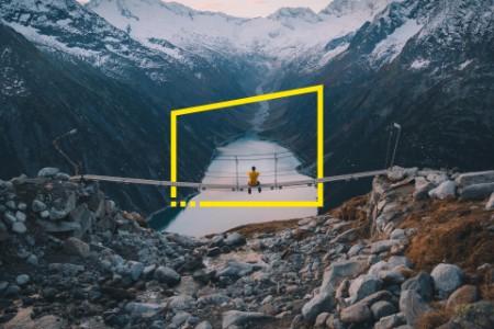 Man som sitter på bro över floden och tittar mot berget