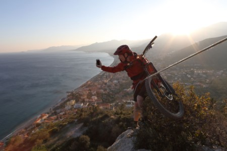mountain biker uses rope to assess route down at sunset