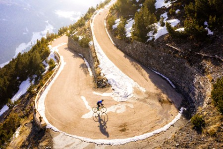 Road cyclist climbing hairpin bends up mountain pass in winter with snow