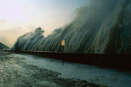 Sign by sea wall as wave crashes