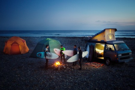 Surfers talk beach camp fire camper vans