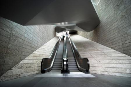 two men standing on a empty escalator