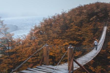 woman crossing suspension bridge in Chile