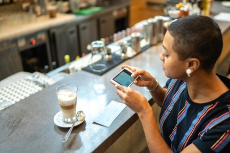 Woman depositing check by phone in the cafe