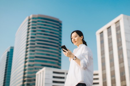 Woman emailing smartphone city clear blue sky