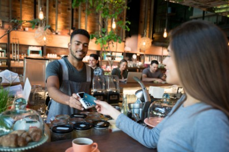 Woman making contactless payment restaurant