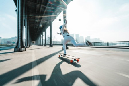 Woman skateboarding under bridge city against sky
