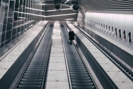 Woman walking up escalator underground station