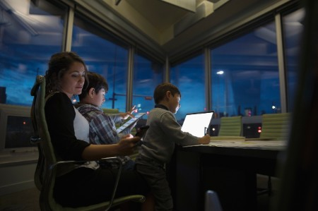 Woman working late sons using digital tablet